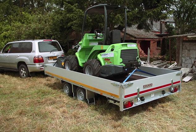 Auto Anhänger EDUARD mit Bagger, Auto Anhänger von EDUARD mit Bordwand, Ladung Baufahrzeug, Ansicht schräg hinten, Aufnahme im Freien