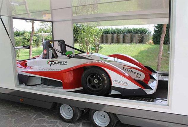 Fahrzeugtransporter beladen mit Rennauto, Turatello Fahrzeugtransporter beladen mit Sportwagen, Ansicht seitlich, Aufnahme im Freien