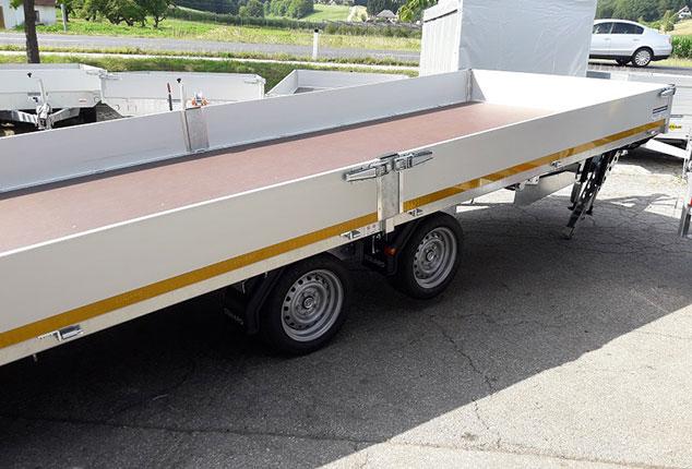 Auto Anhänger EDUARD, 2 Achs Hochlader, Maschinentransporter mit Bordwänden, Ansicht schräg seitlich, Aufnahme im Freien